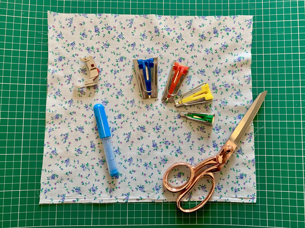 zipper foot, chalk pen, scissors, bias mouse and fabric laid on a green cutting mat