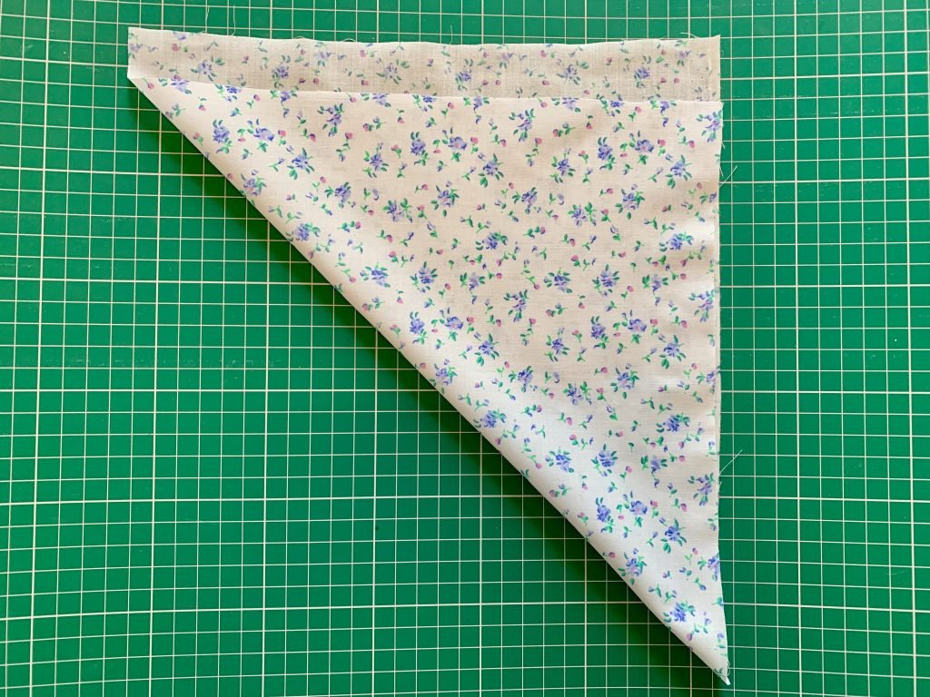 blue and white floral fabric laid in half to make a triangle on the bias on a green cutting mat
