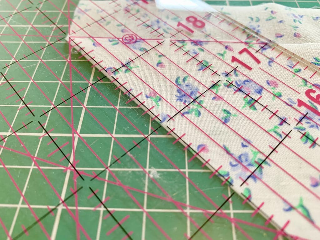 a quilting ruler laid on the folded edge of fabric at 2 inches wide to cut on the bias.
