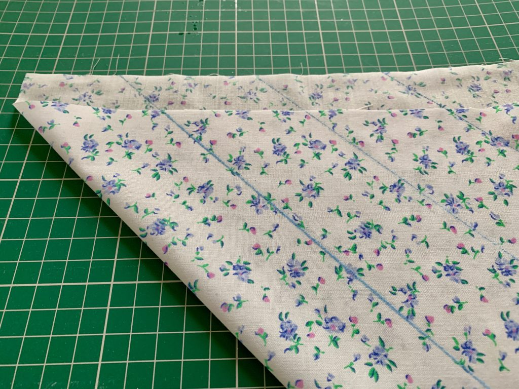 blue and white floral fabric with blue chalk pen lines marked at every 2 inches intervals.