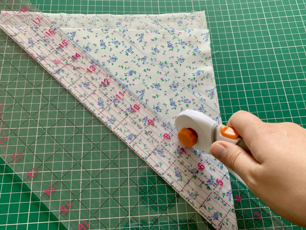 fabric folded on the bias to create bias tape with a quilting ruler and rotarty cutter.