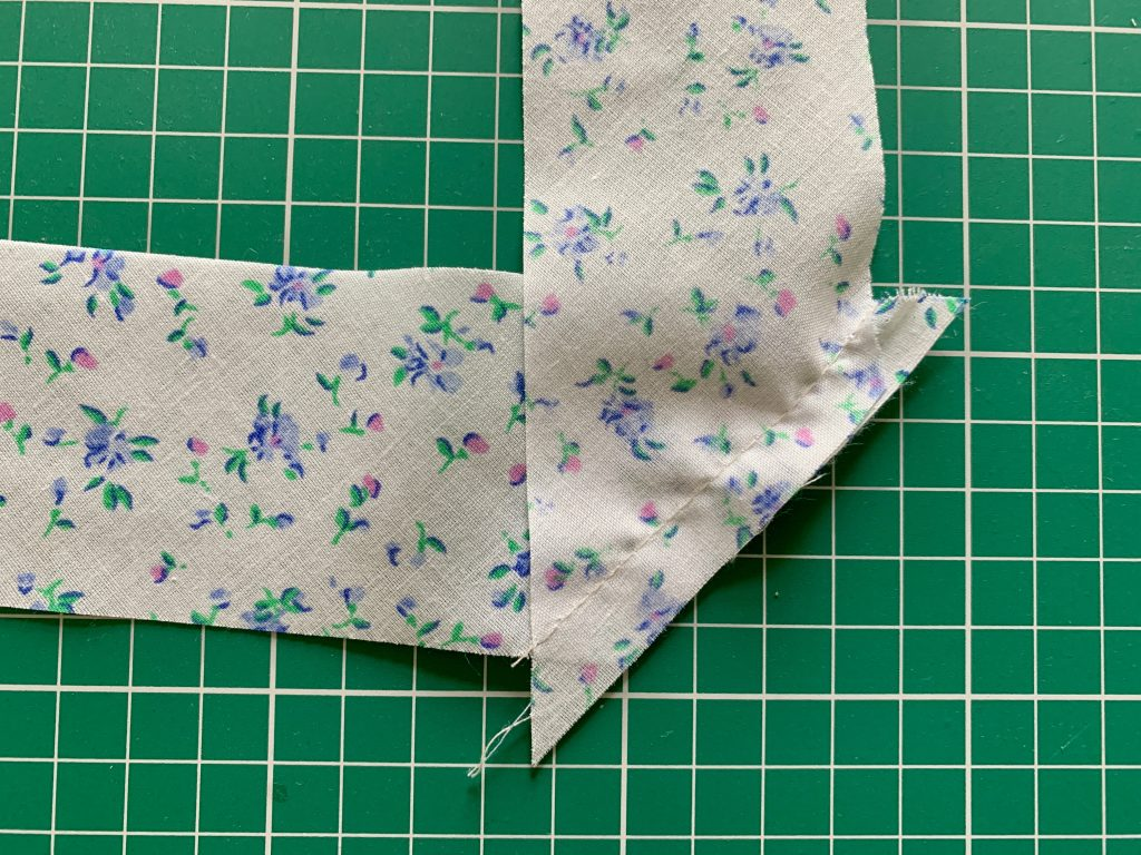 A sewn seam of two pieces of bias tape together at right angles.