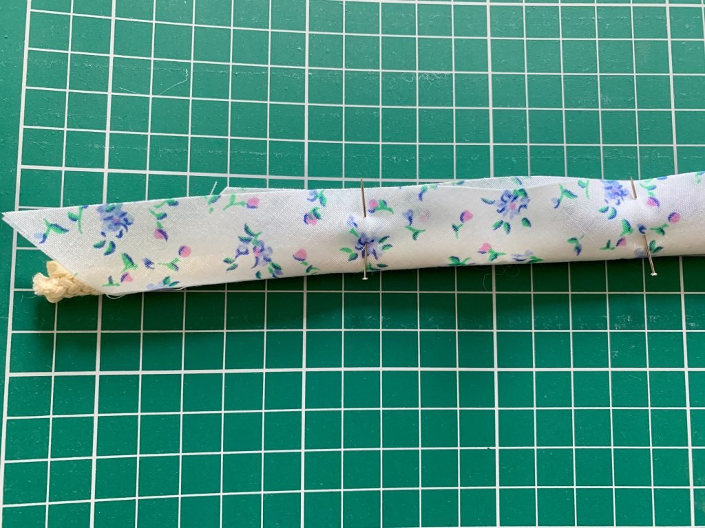 cording pinned into the middle encased with blue and white floral fabric bias tape.