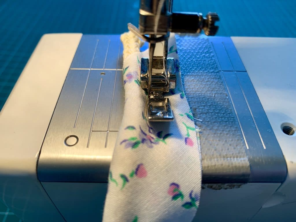 a zipper foot sewing the cording into place within the bias binding to create piping.