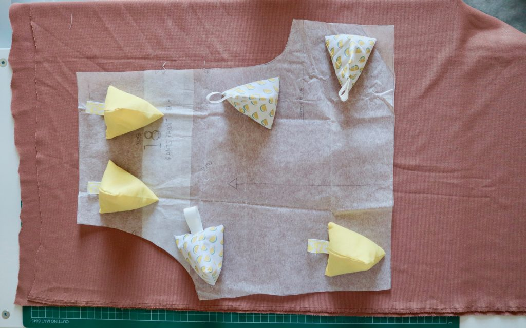 nude fabric with a paper pattern piece in place being held down with yellow pattern weights