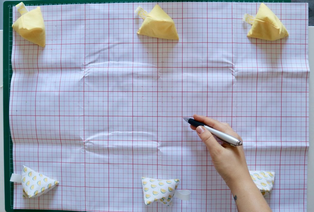 a large piece of squared pattern paper that is held down in place with yellow pattern weights and a hand hold a pen.
