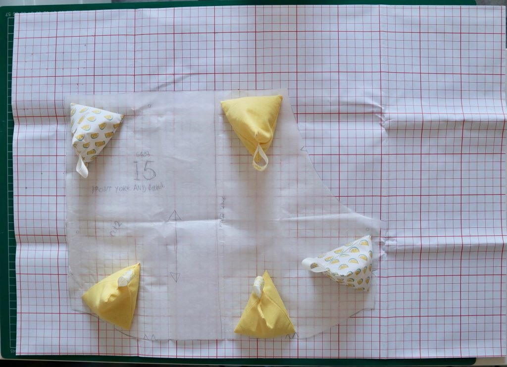 pattern paper with a paper pattern piece on top being held in place with yellow pyramid pattern weights