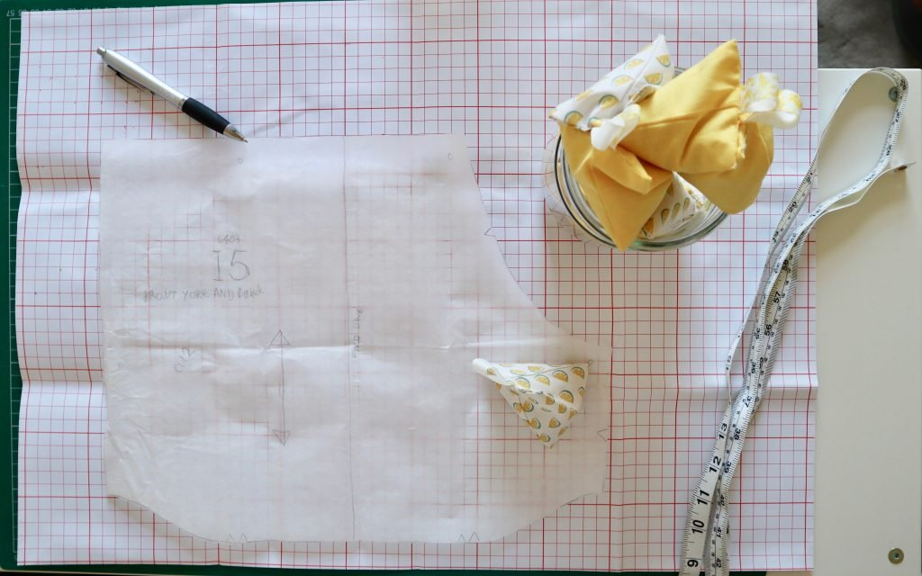 large squared pattern paper with a paper pattern piece on top with a jar of yellow pattern weights, tape measure and pen on the table