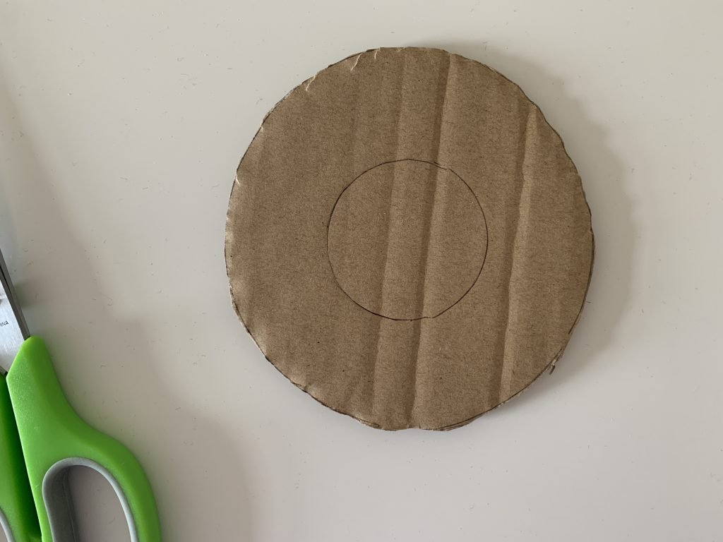 A large circle piece of cardboard with a smaller circle  drawn on for how to make a pom pom maker out of cardboard.