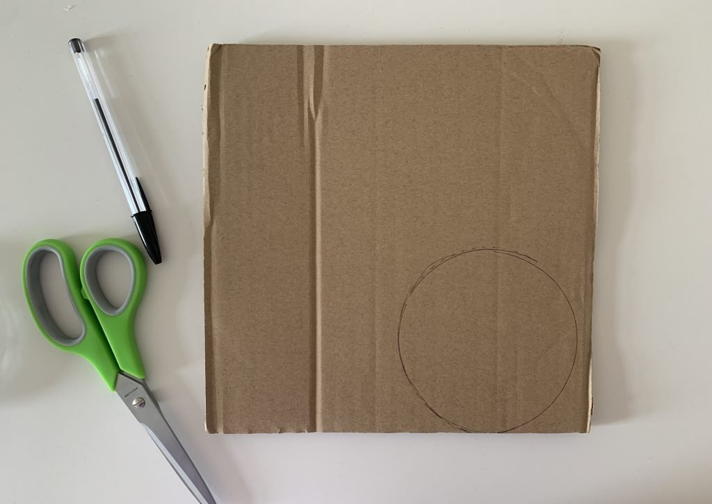 Cutting a cardboard circle for how to make a pom pom maker out of cardboard.