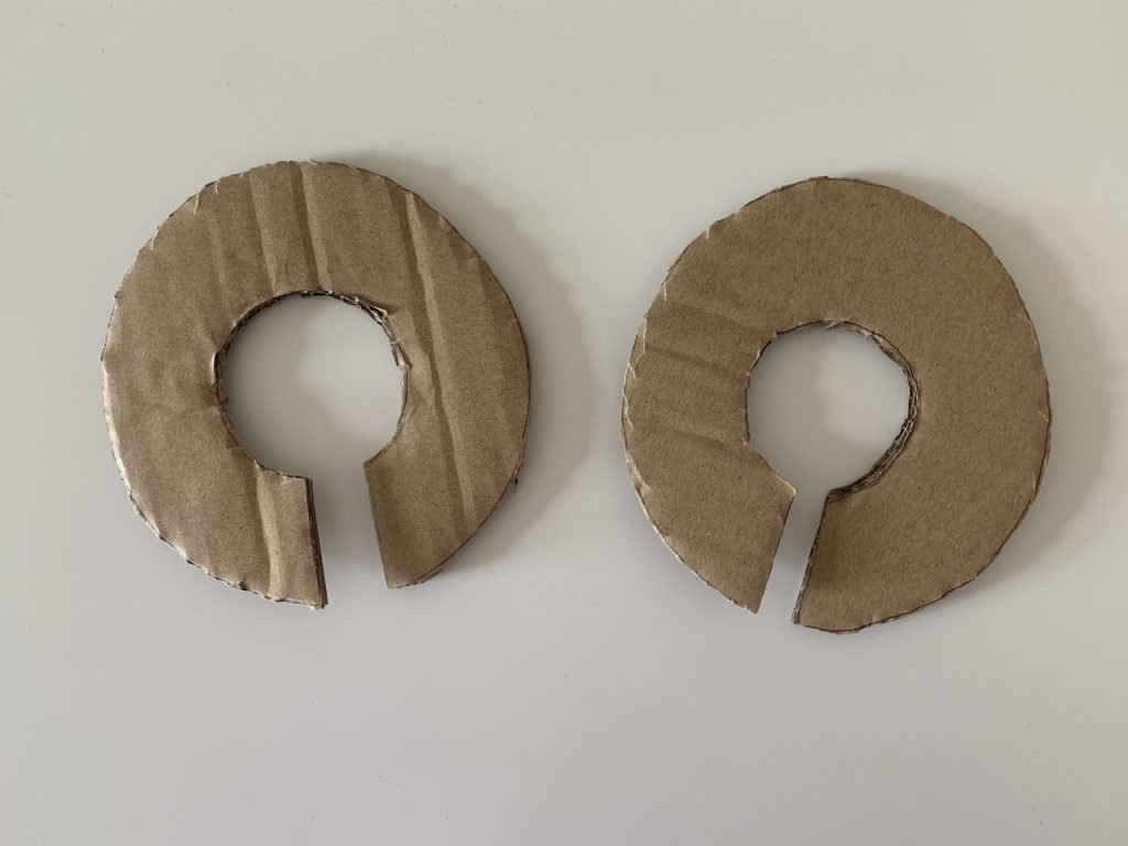 two donut shape pieces of cardboard.
