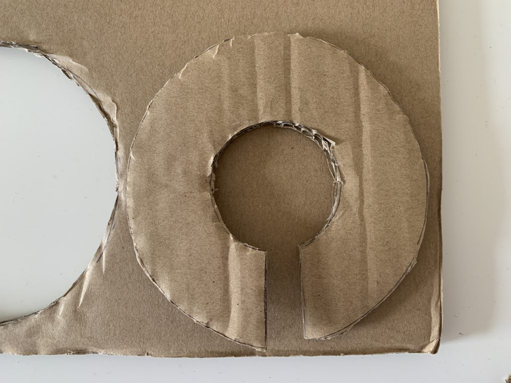 A donut shape piece of cardboard on top of another piece of cardboard to trace out how to make a pom pom maker out of cardboard.