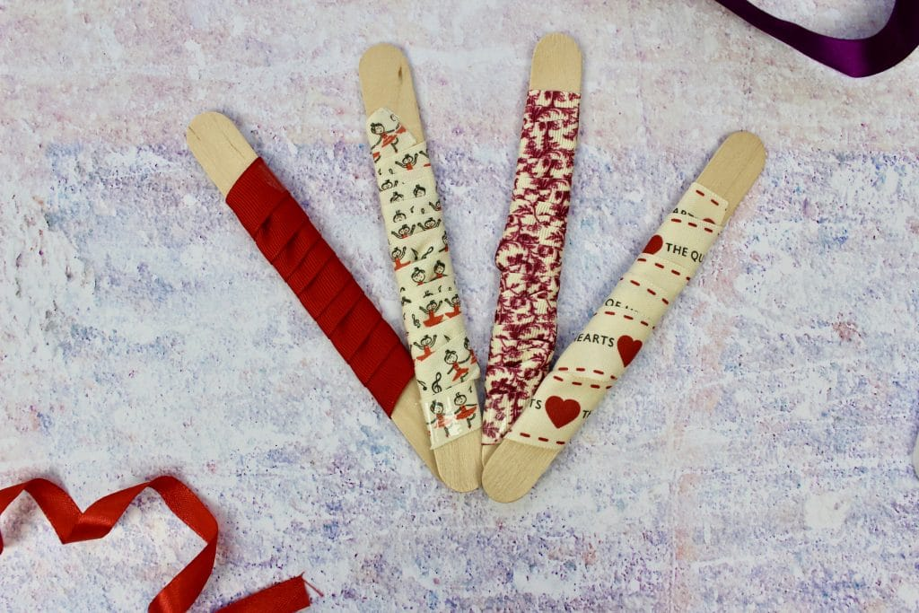 4 large wooden lollypop sticks with red ribbons wrapped around each on on a purple marble background.