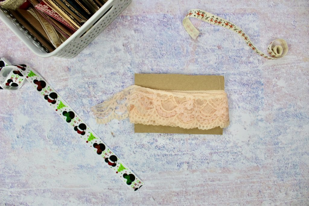 A piece of card with blush pink lace wrapped around it on a purple background.