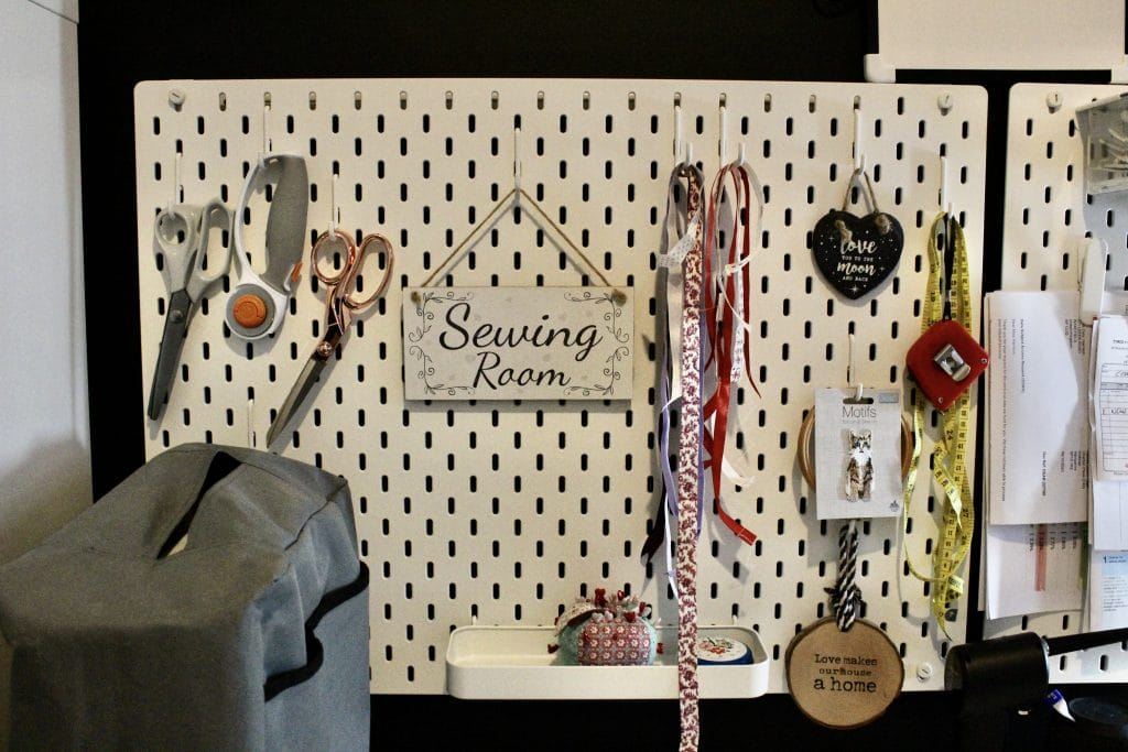 a white peg board full of sewing and craft supplies including ribbon, tape measure and scissors.