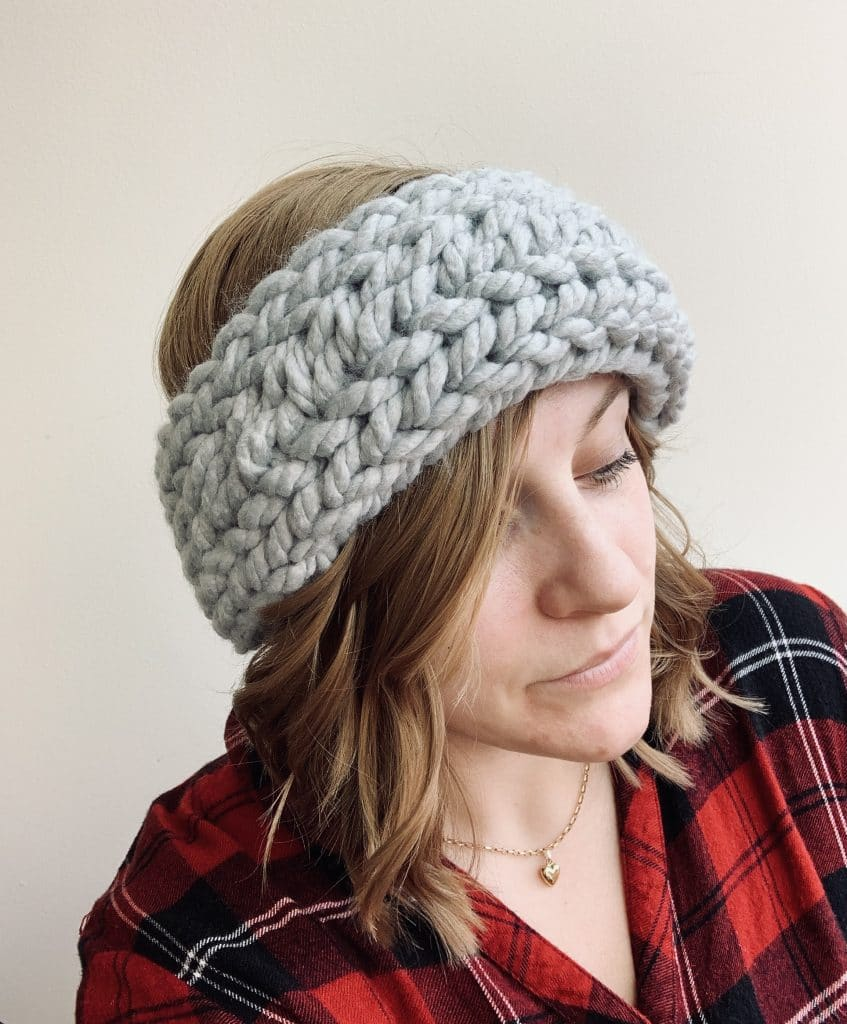 a young woman wearing a chunky grey knitted ear warmer headband with a white background