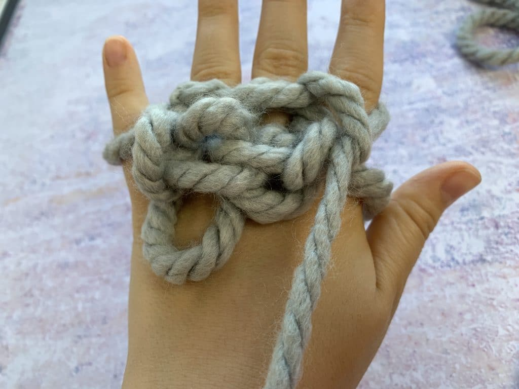 Finger knitting used on an adults hand with grey chunky yarn which is loose and tangled.