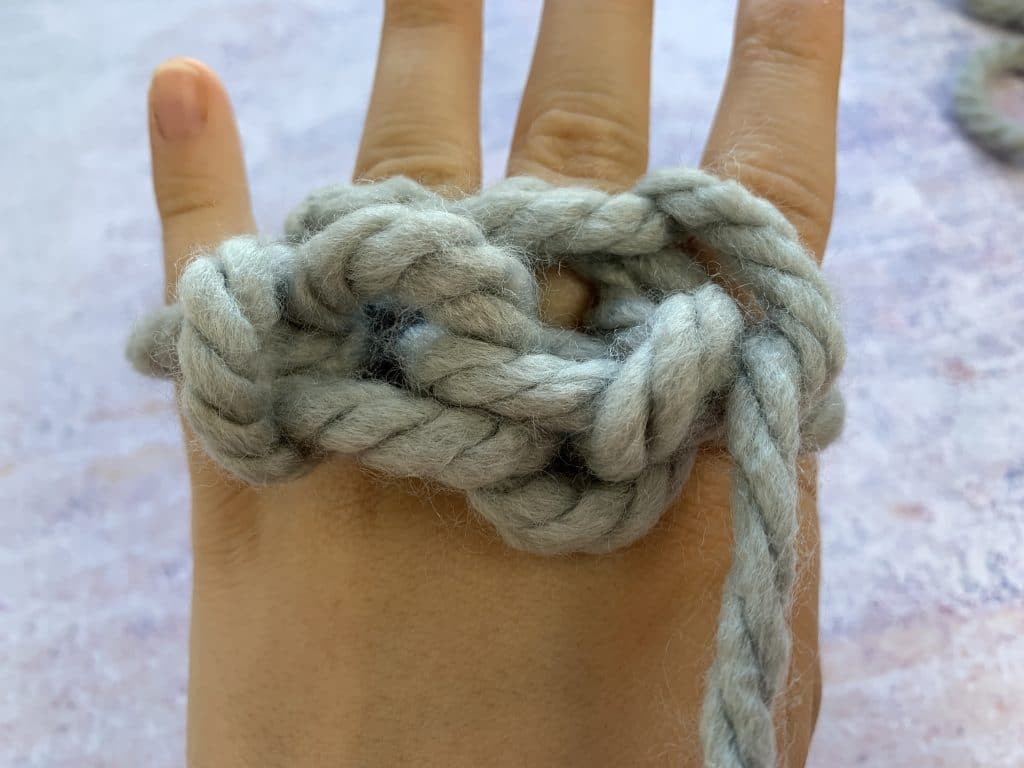 Grey chunky yarn knitted on a hand showing the stitches on the back pulled taught.