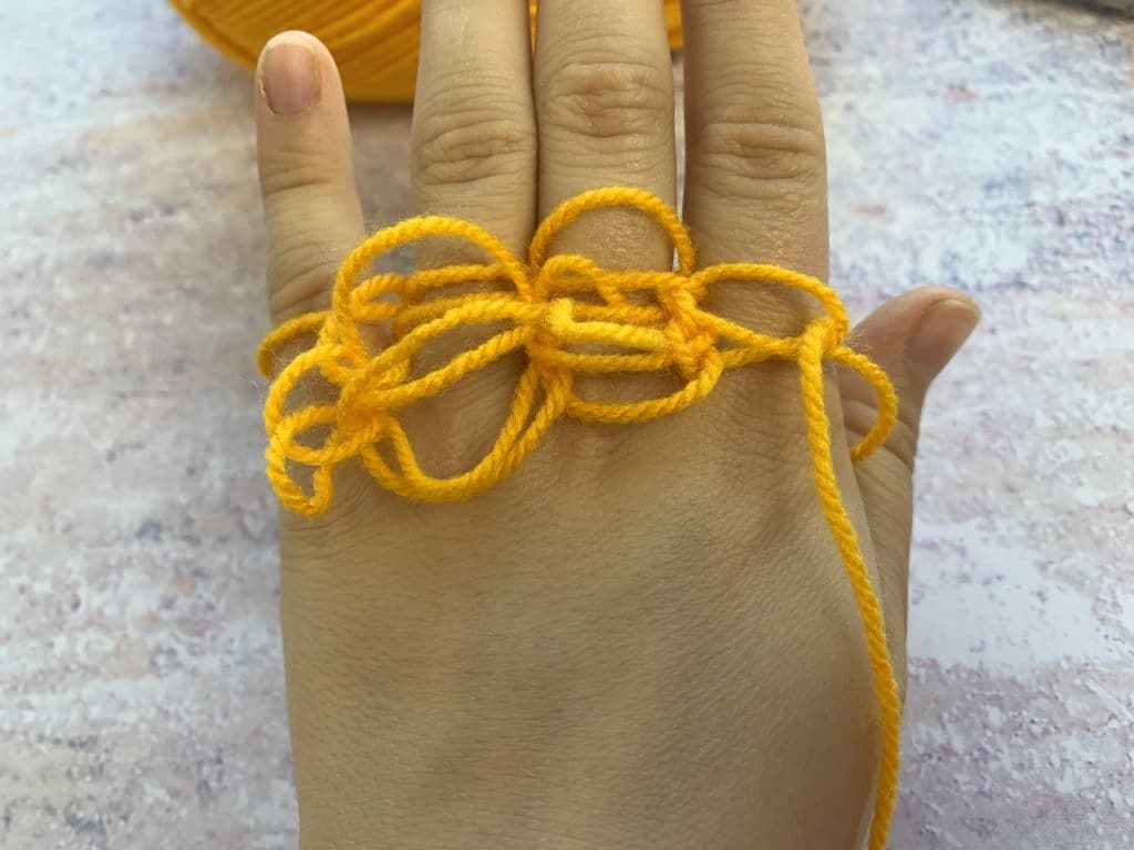 a hand displaying thin yellow yarn finger knitting which is loose and messy.