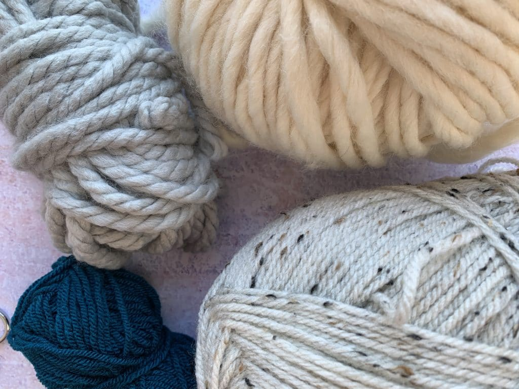 a close up of 4 different yarns from super chunky, chunky, aran and DK in a variety of colours.